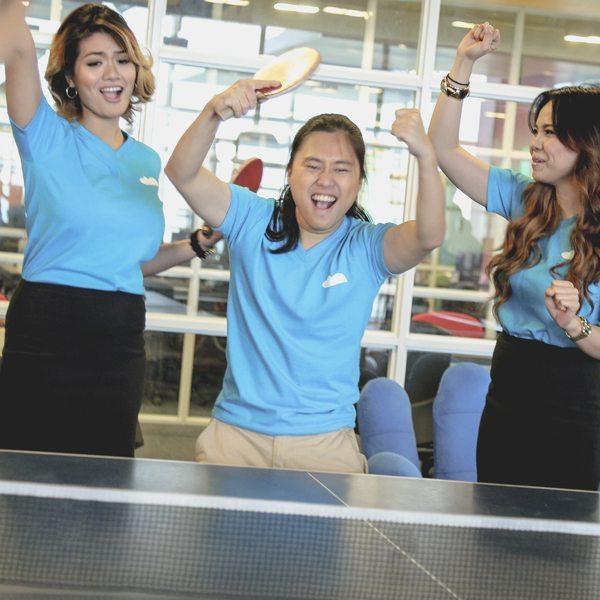Three people cheering at a ping-pong table